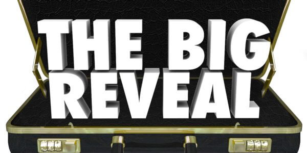 "Open suit case with text ""the big reveal"""